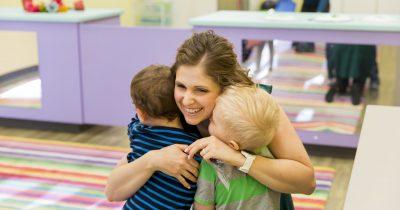 Woman hugging toddlers